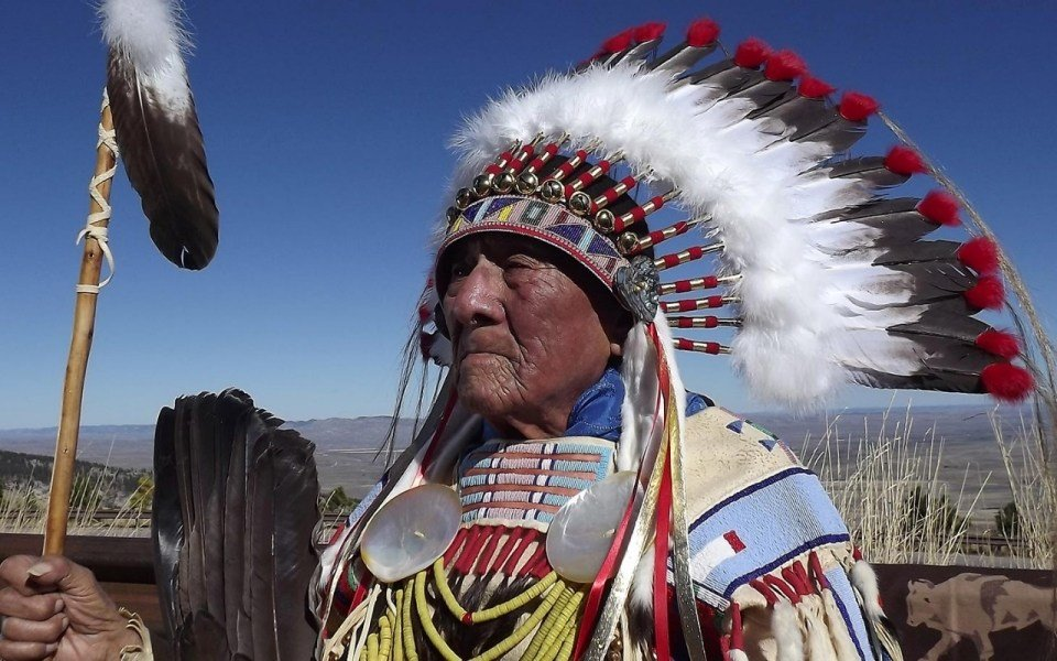 In this family photo, Joseph Medicine Crow wears a headdress beaded by his granddaughter and a war shirt from the Custer Battlefield Trading Post in Crow Agency, Montana. The Bighorn Mountains are in the background. (Photo by Ramona Medicine Crow)