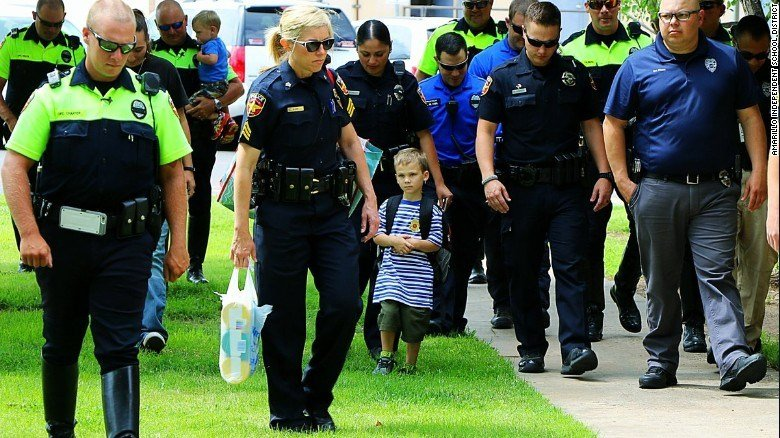 Jackson Scherlen walks with members of Amarillo police on his first day of school.