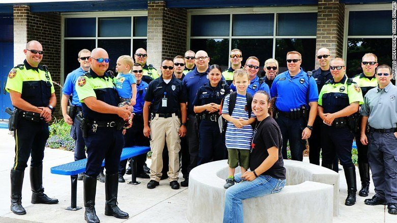 Jackson Scherlen (in striped shirt), and his mother Jessica Scherlen, with members of the Amarillo police.