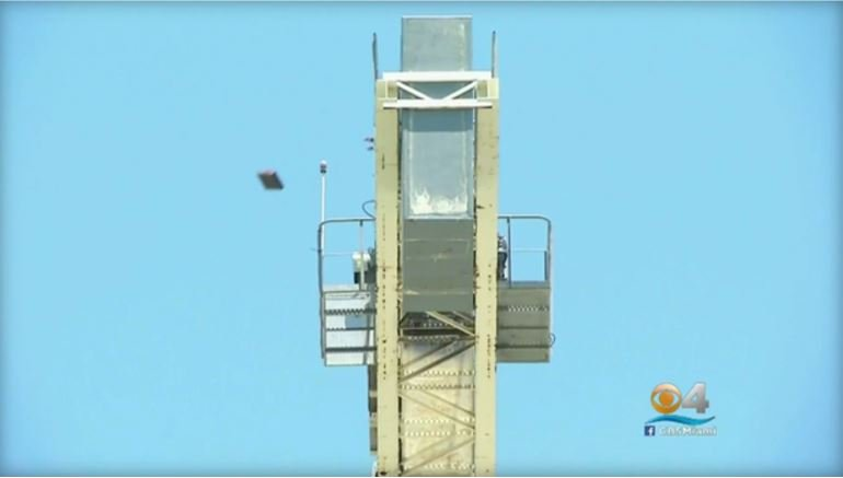 An object is seen falling from a crane that police in Hollywood, Florida say 27-year-old Travis Bernard stood atop, throwing items down on Sunday, July 23, 2017, for more than 10 hours.  CBS MIAMI