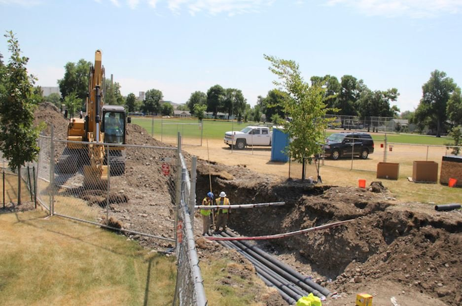 """Workers with General Contractors Construction were on the job in South Park Wednesday, working on the creation of a """"splash pad"""" between the South Park playground and swimming pool. (Ed Kemmick/Last Best News)"""
