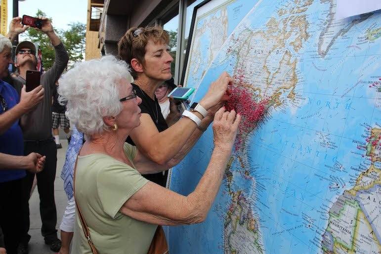 A couple of visitors put pins on a huge map behind the visitors booth on Second Street in Casper, Wyo., showing where they've come from to see the eclipse. (Ed Kemmick/Last Best News)