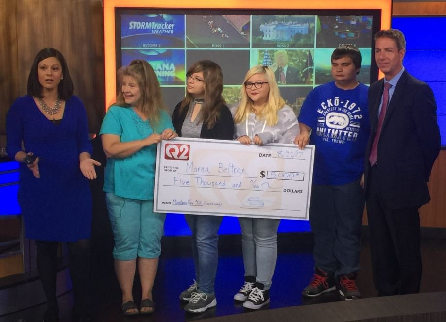 Montana This Morning Anchor Victoria Hill and Q2 General Manager Shawn Wilcox present Marna Beltran and her family a check for $5K during the morning show on Tuesday.