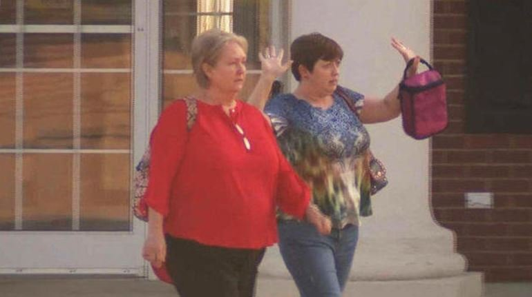 Two women who were held hostage exit a bank in Columbia, Tennessee, on Friday, Sept. 22, 2017 (CBS News)