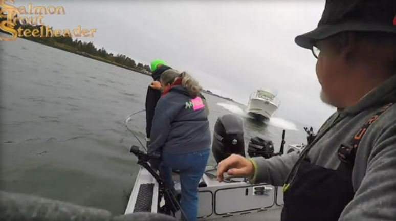 Still from video posted on magazine Salmon Trout Steelheader's Facebook page shows moments before three people leaped for their lives from their boat as another barreled down on theirs.