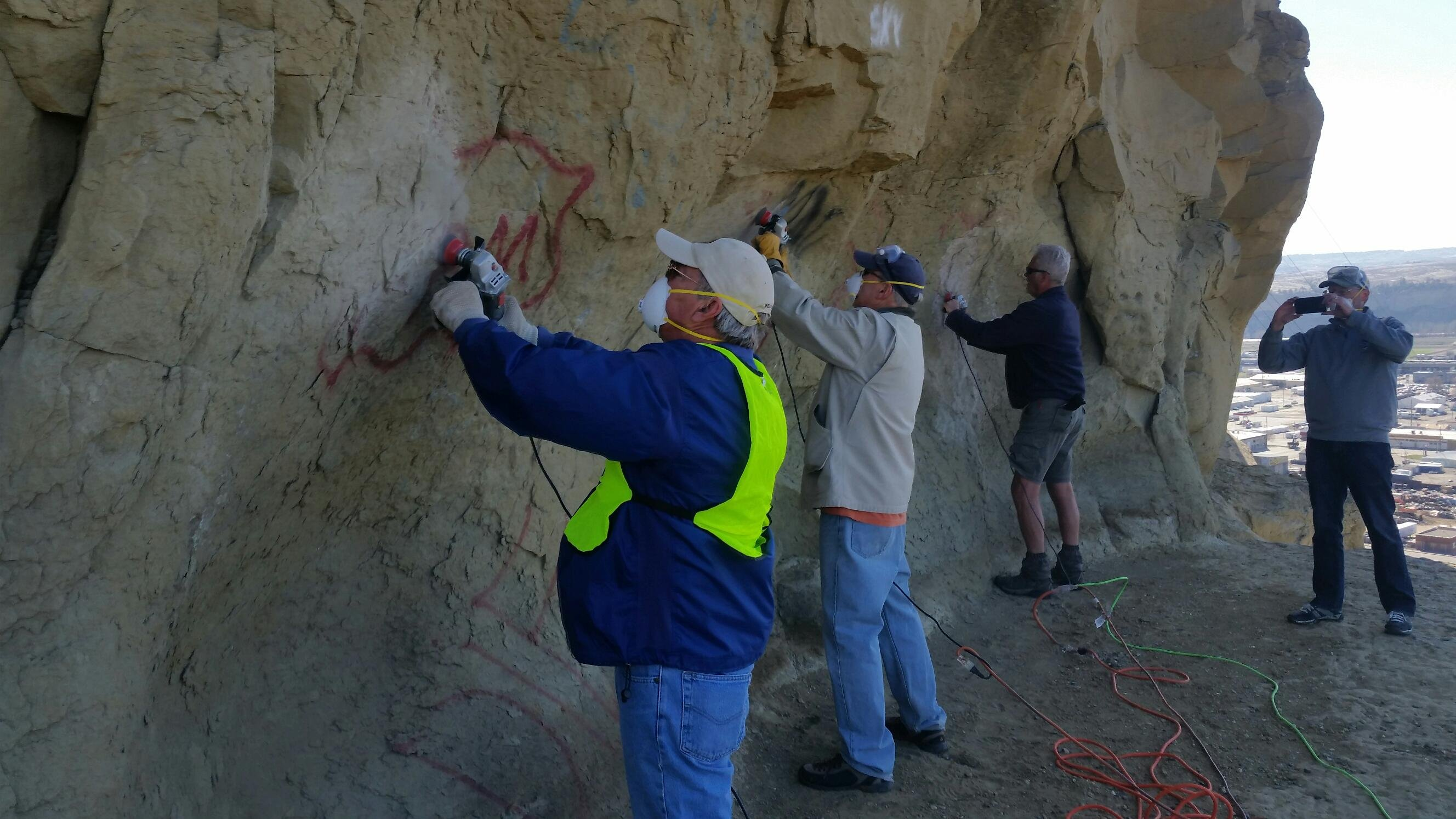 Rotarians Frank Witt, Jon Doak and Dave Lundin work with grinders remove graffiti from the sandstone face the Rims. (Photo courtesy of Christ Waite)