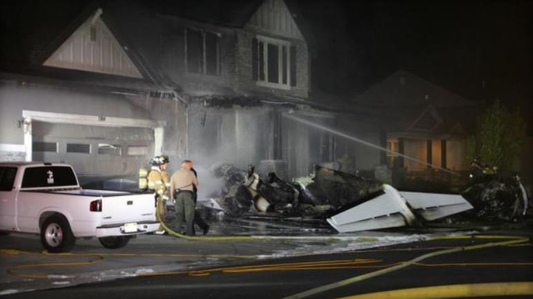 A small plane crashed into a house in central Utah early Monday morning and the pilot has died, officials confirmed to CBS affiliate KUTV. /  BRENT CHRISTENSEN/KUTV