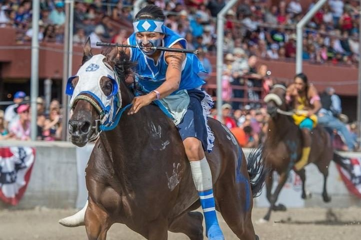 His quirt in his teeth, a rider tears down the track. (Photo credit: John Warner)