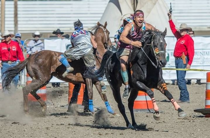 One rider springs to a good start while another jockey struggles to mount his pony. (Photo credit: John Warner)