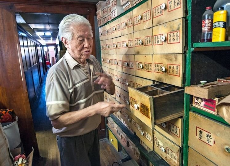 Pekin owner Danny Wong opens an old herb drawer in what used to be an herb dispensary on the building's ground floor. (John Warner)