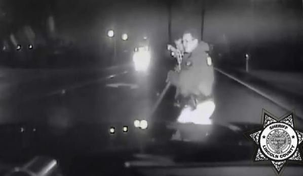 Deputy Jeremy Gautney scoops up tot he found running down Oregon highway. KOIN