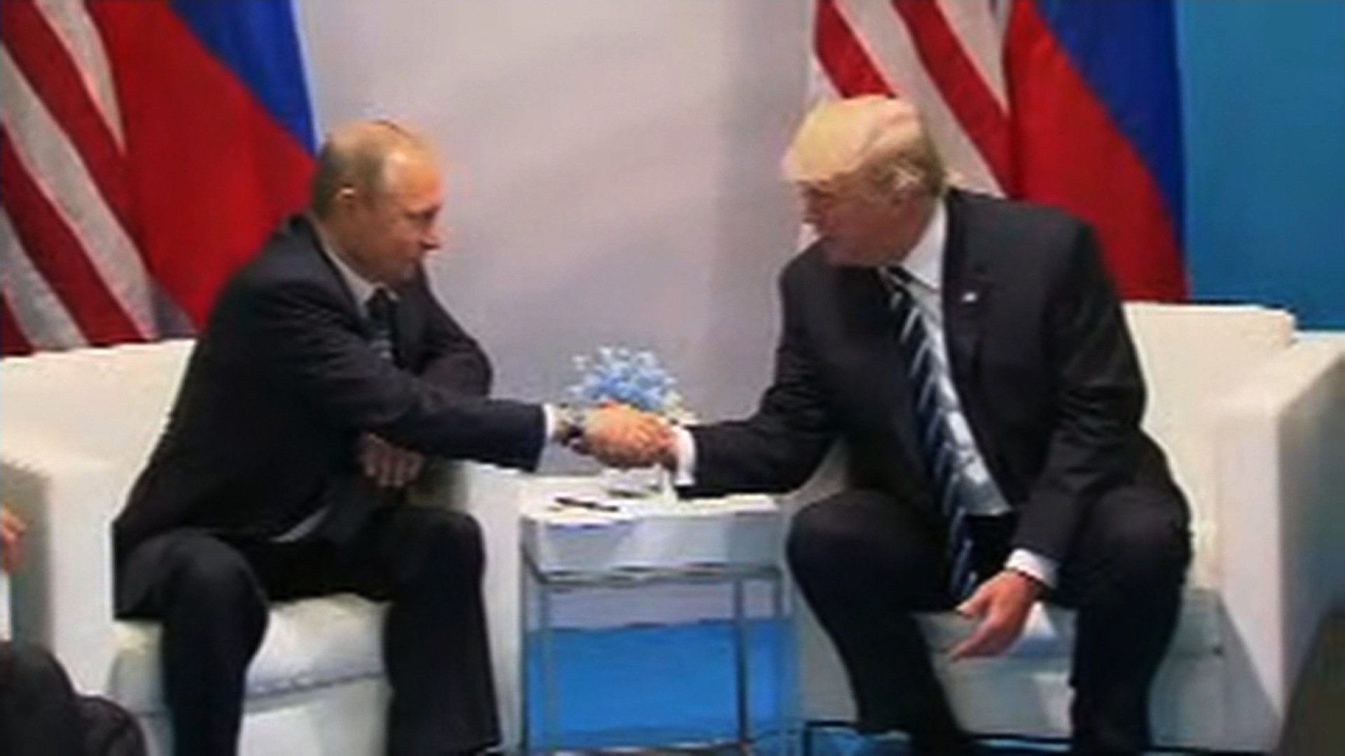 (File Photo) President Donald Trump shakes hands with Russian President Vladimir Putin at the G20 Summit, Friday, July 7, 2017, in Hamburg. courtesy Host TV.